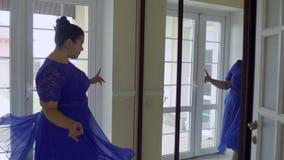 Тучная девушка в голубом платье перед зеркалом видеоматериал
