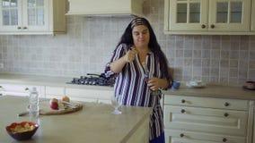 Тучная девушка в кухне видеоматериал