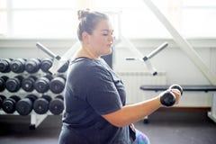 Тучная девушка в спортзале стоковые изображения rf