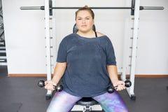 Тучная девушка в спортзале стоковые фотографии rf