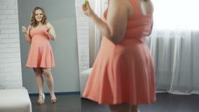 Тучная девушка есть сладостные donuts перед зеркалом, полностью удовлетворенным с ей взгляд сток-видео