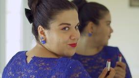 Тучная девушка красит ее губы перед зеркалом видеоматериал