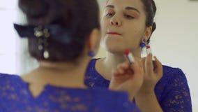 Тучная девушка красит ее губы перед зеркалом сток-видео