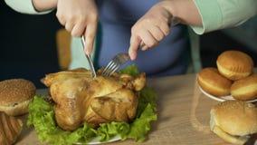 Тучная женщина высекая грубо жареный цыпленка при вилка и нож, есть высококалорийную вредную пищу акции видеоматериалы