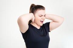 Тучная женщина в sportswear покрывая ее уши и кричать Стоковые Фото