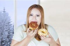 Тучная женщина есть 2 donuts Стоковая Фотография RF
