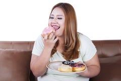 Тучная женщина ест донут на плите Стоковое Изображение