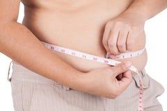 Тучная женщина измеряя ее живот на белой предпосылке Стоковые Изображения RF