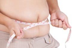 Тучная женщина измеряя ее живот на белой предпосылке Стоковое Изображение