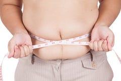 Тучная женщина измеряя ее живот на белой предпосылке Стоковая Фотография