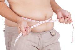 Тучная женщина измеряя ее живот на белой предпосылке Стоковое Фото