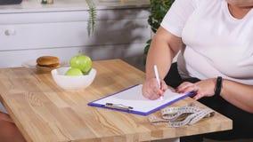 Тучная женщина подписывая контракт с диетологом Стоковые Фотографии RF