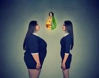 Тучная женщина смотря тонкую девушку пригонки Концепция питания диеты отборная правая стоковое изображение rf