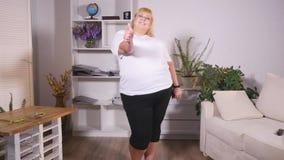 Тучная женщина стоит на масштабах, танцах и выставки классифицируют видеоматериал
