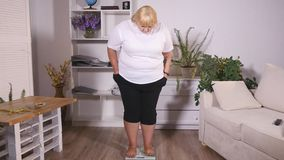 Тучная женщина стоит на масштабах видеоматериал