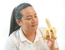 Тучная женщина с бананом стоковые изображения