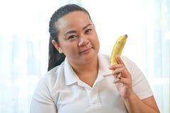 Тучная женщина с бананом стоковые фото