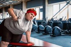 Тучная потная женщина используя гантели в спортзале Стоковые Фотографии RF