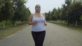 Тучные бега девушки вдоль дороги сток-видео