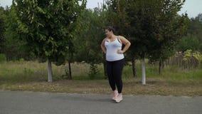 Тучные бега девушки вдоль дороги акции видеоматериалы