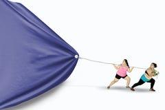 Тучные женщины волочат большой флаг Стоковые Изображения