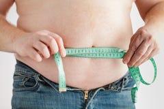 Тучный живот человека с измеряя лентой изолированный зеленый цвет принципиальной схемы пачки спаржи теряет вес ленты Стоковое фото RF