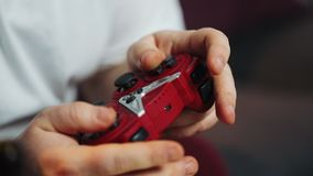 Тучный человек держит gamepad в его оружиях, конце-вверх, играх консоль игры Концепция видеоигры видеоматериал
