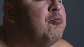 Тучный человек жуя еду delightfully, невозможность контролировать потребление высококалорийной вредной пищи видеоматериал