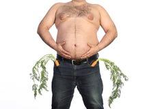 Тучный человек держа морковь стоковые фото