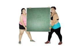 2 тучных женщины держа доску на студии Стоковое Изображение