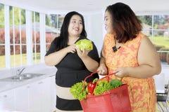 2 тучных женщины с овощами в кухне Стоковое фото RF