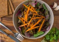 Тушёное мясо в плите с салатом выходит на деревянный стол Стоковые Изображения