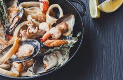 Тушёное мясо морепродуктов в крупном плане кастрюльки на темной деревянной предпосылке Стоковая Фотография RF