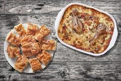 Тушёное мясо цыпленка Vegetable в лотке выпечки и Plateful традиционных скомканных Gibanica кусков пирога сыра на старом выдержан Стоковая Фотография