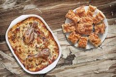 Тушёное мясо цыпленка Vegetable в лотке выпечки с Plateful Gibanica скомкало куски пирога сыра на старой треснутой облупленной та Стоковые Изображения