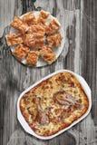 Тушёное мясо цыпленка Vegetable в лотке выпечки с Plateful Gibanica скомкало куски пирога сыра на старой треснутой облупленной та Стоковые Фото