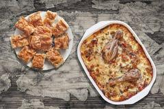 Тушёное мясо цыпленка Vegetable в лотке выпечки с Plateful Gibanica скомкало куски пирога сыра на старой треснутой облупленной та Стоковая Фотография