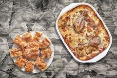 Тушёное мясо цыпленка Vegetable в лотке выпечки с Plateful Gibanica скомкало куски пирога сыра на старой треснутой облупленной та Стоковые Изображения RF