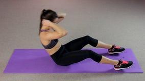 Тщательная молодая женщина работая крепко для того чтобы иметь идеальное тело, делая подбрюшные хрусты видеоматериал