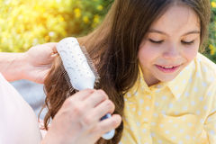 Тщательная беременная женщина расчесывая волосы девушки Стоковые Изображения RF