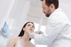 Тщательный ведущий специалист изменяя его взгляд пациентов Стоковые Изображения