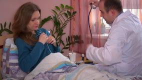 Тщательный мужской доктор проверяя пациента ИМПа ульс и рассматривать женского с стетоскопом сток-видео