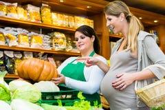 Тыква и овощи женщины покупая в деликатесе Стоковая Фотография