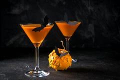 Тыква с летучими мышами черноты и оранжевый коктеиль в стекле на хеллоуине стоковое изображение