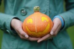 Тыква хеллоуина в женских предназначенных для подростков руках стоковые изображения