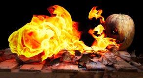Тыква хеллоуина извергая пламена огня на черной предпосылке Стоковые Фото