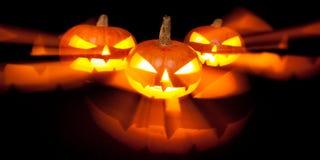 3 тыквы Джек-o-фонарика накаляя в темноте Стоковая Фотография