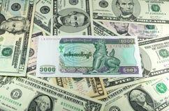 Тысяча кьятов Мьянмы на предпосылке много долларов Стоковое Изображение RF