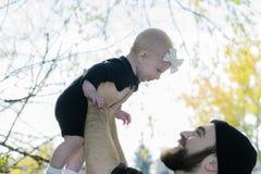 Тысячелетний папа держа дочь младенца вверх показывая привязанность Стоковая Фотография
