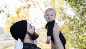 Тысячелетний папа держа дочь младенца вверх показывая привязанность Стоковая Фотография RF